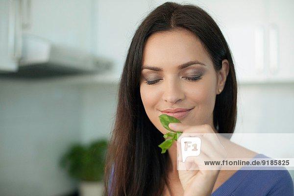 Porträt einer jungen Frau  die Basilikum riecht