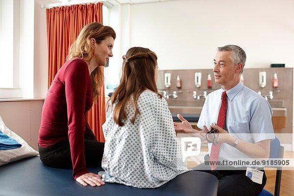 Arzt im Gespräch mit Patient und Mutter