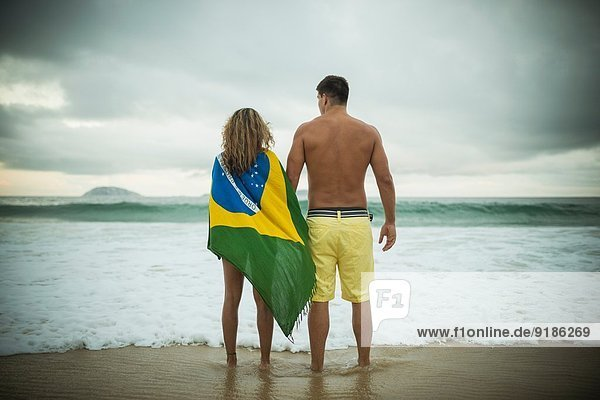 Young couple  woman wrapped in brazilian flag  Ipanema Beach  Rio de Janeiro  Brazil