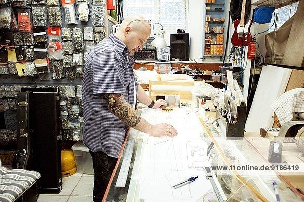 Gitarrenbauer beim Vermessen des Entwurfs auf dem Zeichentisch