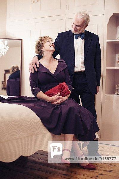 Paar im Schlafzimmer  reife Frau auf dem Bett sitzend