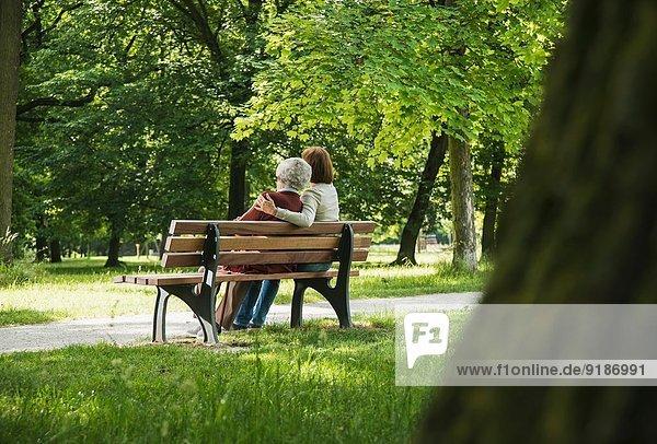 Seniorin sitzend auf Parkbank mit Enkelin