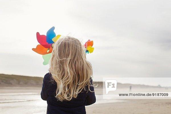 Rückansicht des Mädchens mit Papierwindmühlen am Strand  Bloemendaal aan Zee  Niederlande