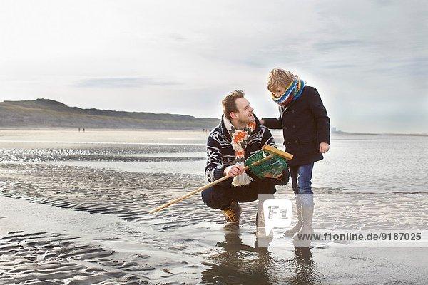 Mittlerer Erwachsener Mann und Sohn mit Fischernetz am Strand  Bloemendaal aan Zee  Niederlande