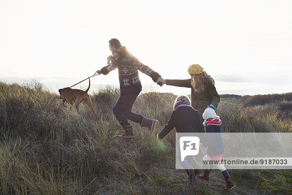Mittleres erwachsenes Paar  das mit seinem Sohn  seiner Tochter und seinem Hund in den Sanddünen spazieren geht.