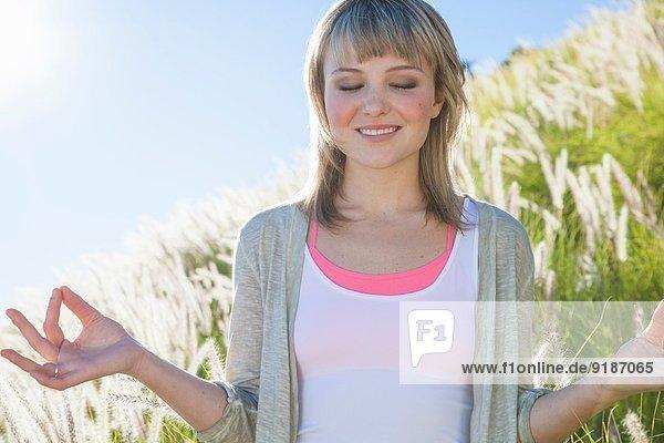 Junge Frau beim Meditieren mit geschlossenen Augen im langen Gras