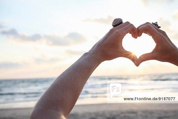 Weibliche Hände  die bei Sonnenuntergang am Strand das Herz in Form bringen.