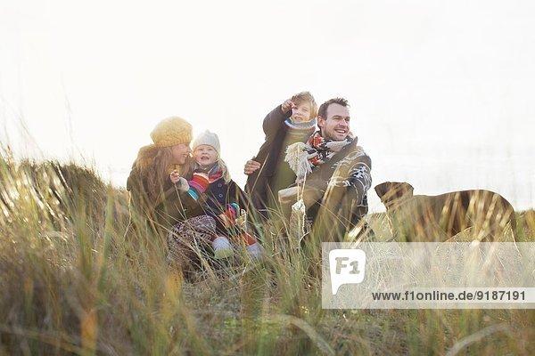 Mittleres erwachsenes Paar in Sanddünen mit Sohn  Tochter und Hund