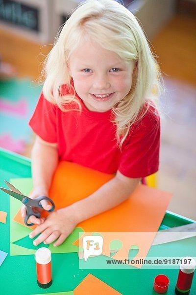 Porträt eines Mädchens beim Schneiden im Kindergarten