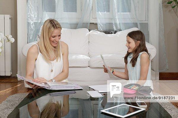 Mutter und Tochter beim Lesen von Notizen im Wohnzimmer