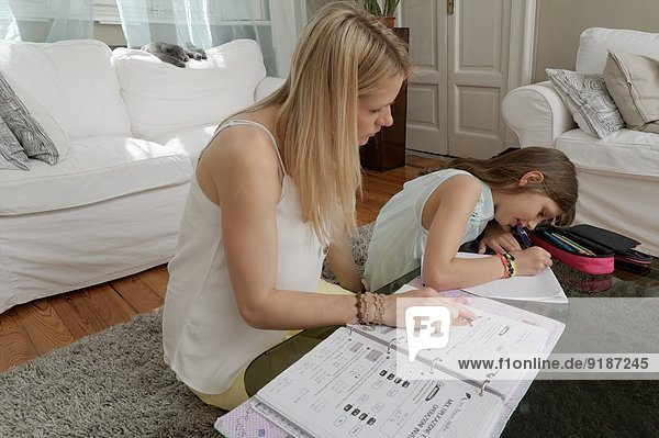 Mother helping daughter with homework on coffee table
