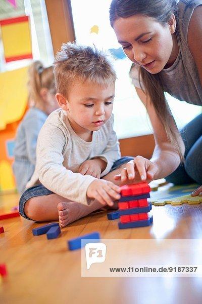 Lehrer und Junge beim Bau von Bausteinen im Kindergarten