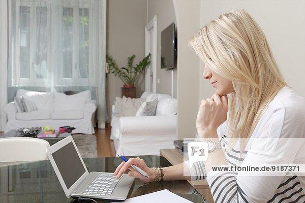 Junge Frau beim Tippen auf dem Laptop zu Hause am Schreibtisch