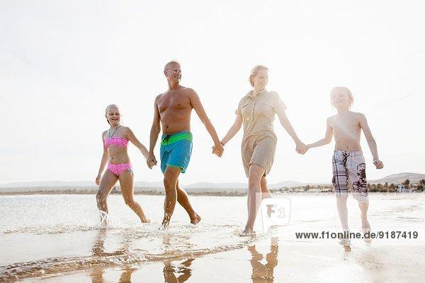 Familie mit zwei Kindern beim Bummeln und Händchenhalten am Strand