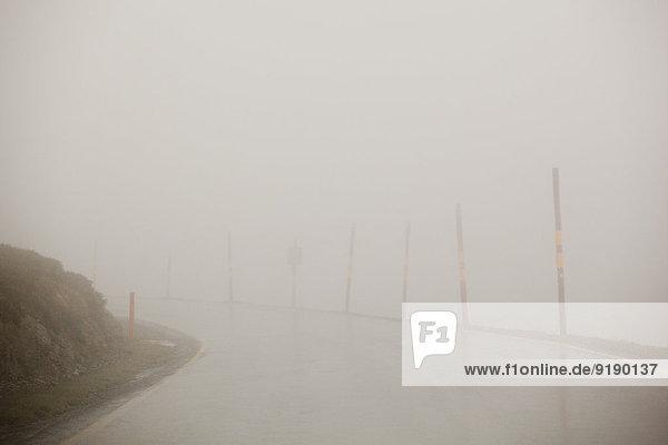 Leere  mit Nebel bedeckte Straße gegen klaren Himmel