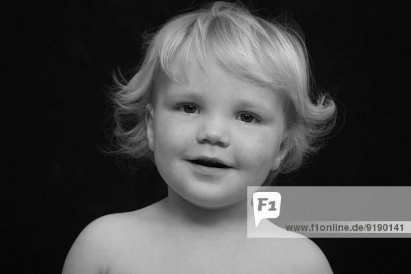 Porträt des süßen Jungen lächelnd auf schwarzem Hintergrund