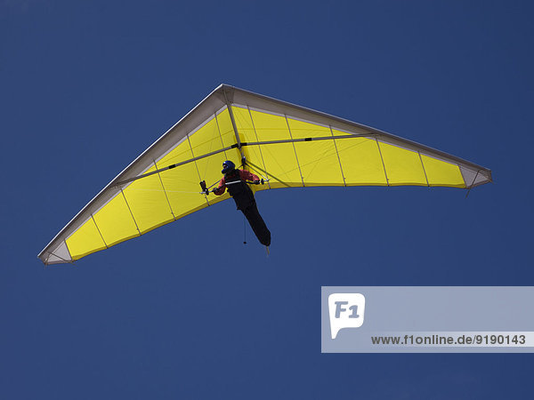 Niederwinkelansicht einer Person beim Drachenfliegen gegen den klaren blauen Himmel