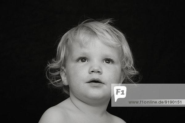 Nachdenklicher Junge schaut weg vor schwarzem Hintergrund