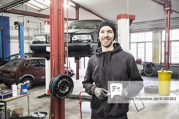Portrait of smiling male mechanic in auto repair shop