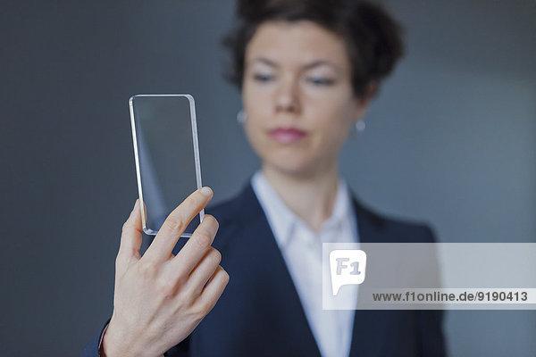 Zuverlässige Geschäftsfrau mit transparentem Smartphone auf farbigem Hintergrund