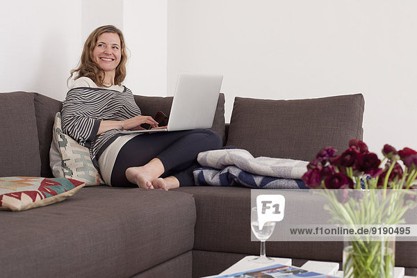 Happy woman looking away while using laptop on sofa