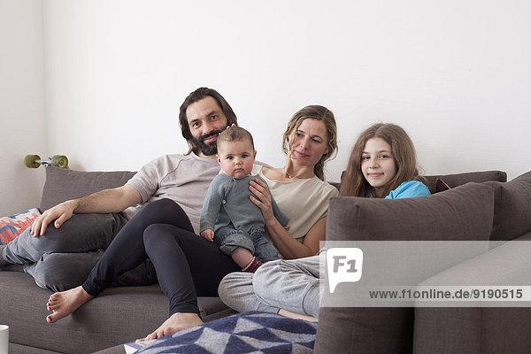 Porträt einer Familie mit zwei Kindern  die auf einem Sofa im Wohnzimmer sitzen.