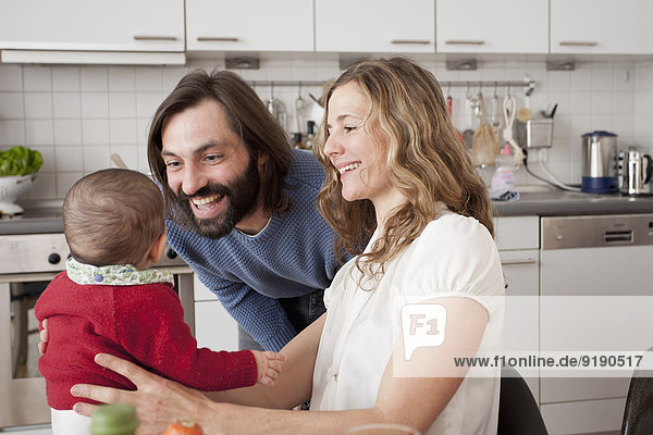 Happy parents with baby girl in kitchen