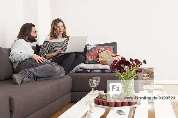 Mittleres erwachsenes Paar mit Laptop auf Sofa im Wohnzimmer