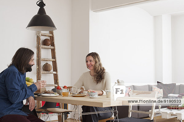 Lächelndes Paar beim Frühstück am Tisch im Haus