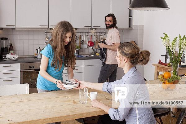 Mann schaut auf die Familie  die Teller auf dem Tisch in der Küche anordnet.