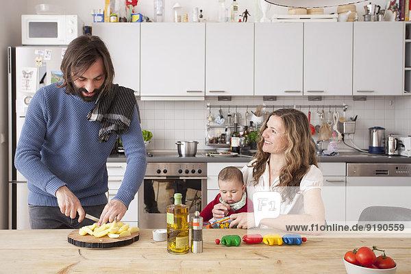 Vater hackt Gemüse mit Frau und Mädchen in der Küche