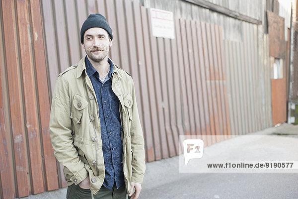 Nachdenklicher junger Mann mit Hand in der Tasche im Freien stehend
