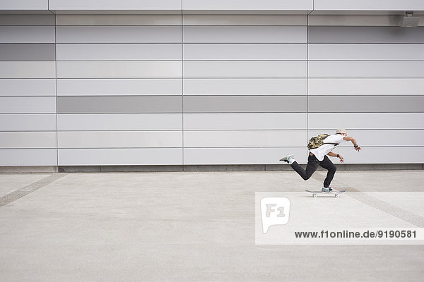 Volle Länge des Mannes Skateboarding im Freien