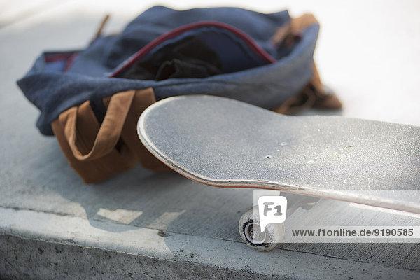 Nahaufnahme von Skateboard und Tasche auf dem Bürgersteig
