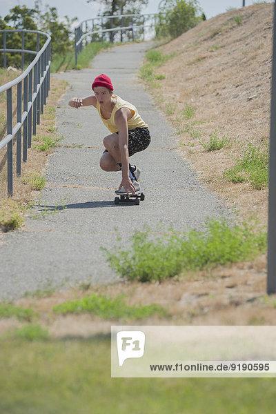 Volle Länge des Mannes Skateboarding auf dem Fußweg