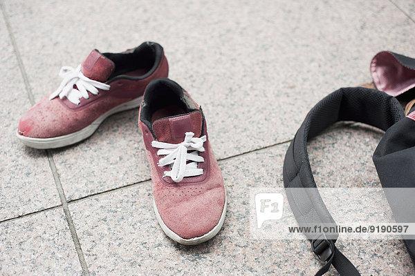 Hochwinkelansicht von Schuhen und Tasche auf dem Boden