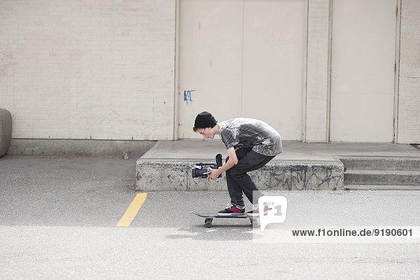 Volle Seitenansicht des Mannes beim Skateboarden im Freien