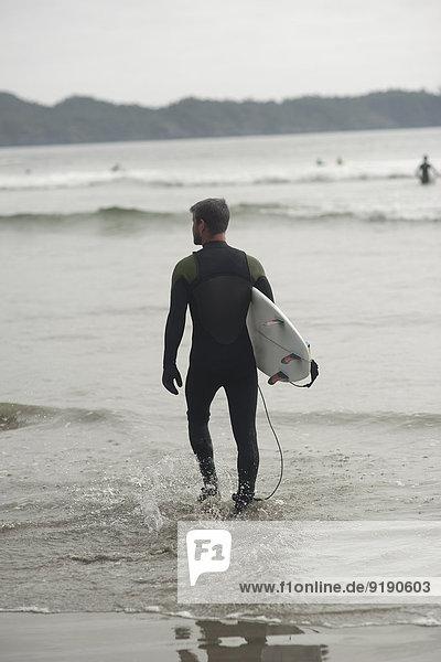 Durchgehende Rückansicht des Mannes mit Surfbrett im Wasser am Strand