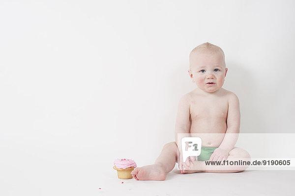 Porträt eines süßen Babys mit Muffin auf weißem Hintergrund
