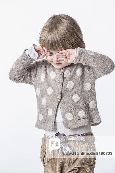 Süßes Mädchen reibt die Augen vor weißem Hintergrund.