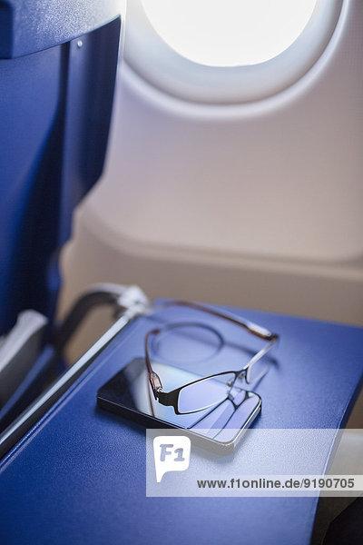 Smartphone und Brille auf dem Tisch im Flugzeug