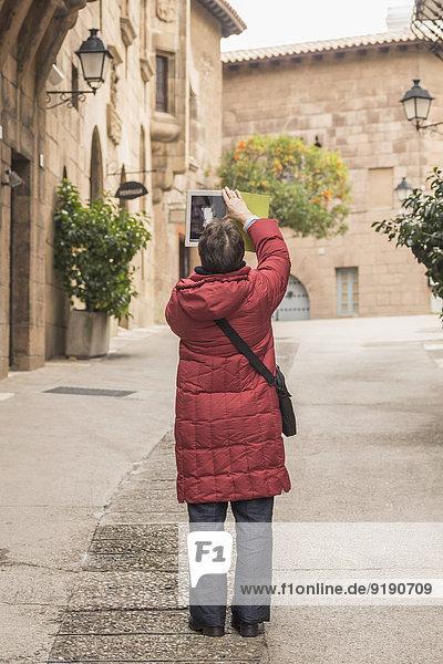 Volle Länge der Frau beim Fotografieren von Gebäuden mit digitalem Tablett