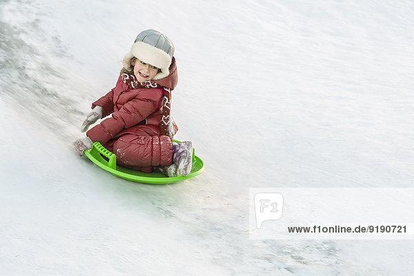 Volle Länge des fröhlichen Mädchenrodelns im Schnee