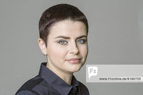 Porträt einer selbstbewussten mittleren erwachsenen Frau vor grauem Hintergrund