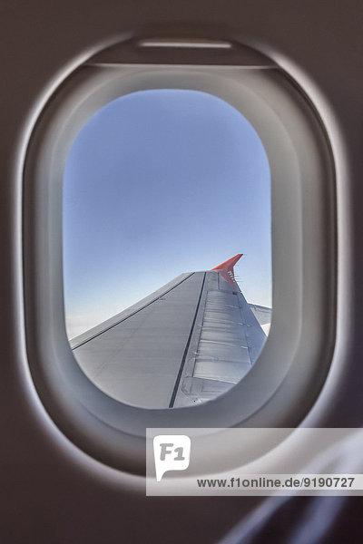 Ansicht des Flugzeugflügels durch das Fenster
