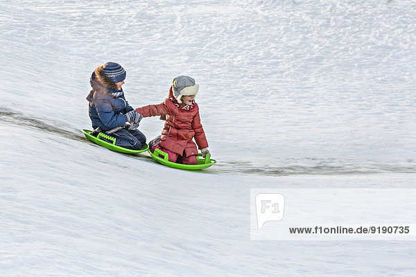 Volle Länge der Geschwister beim gemeinsamen Rodeln im Schnee