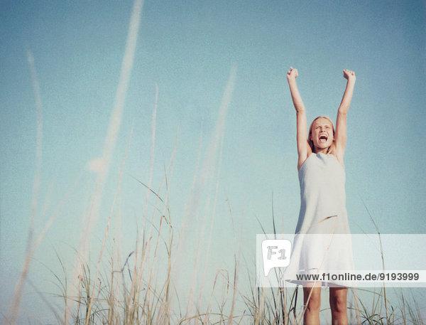Junge Frau im Feld stehend mit erhobenen Armen  schreiend  Blickwinkel niedrig