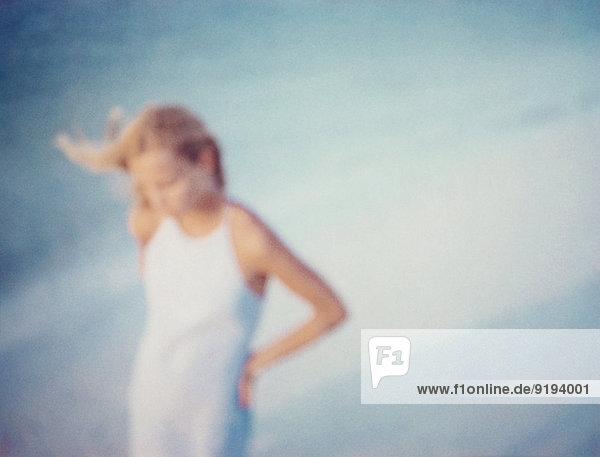 Frau geht alleine am Strand  defokussiert