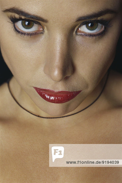 Frau in schwerem Make-up  starrt in die Kamera.