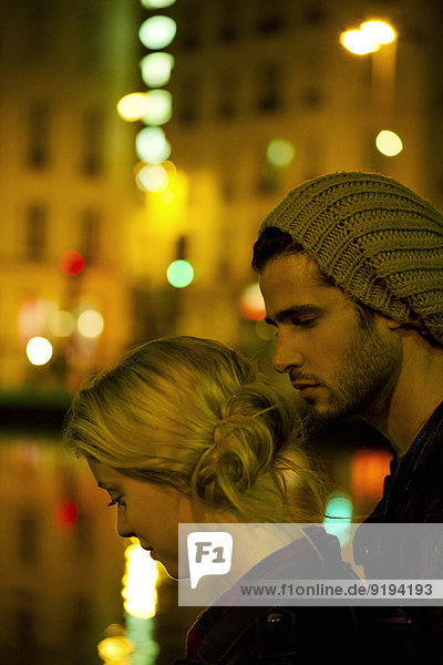 Young couple at night by river illuminated by city lights